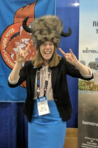 woman wearing conference badge and large fur hat with horns